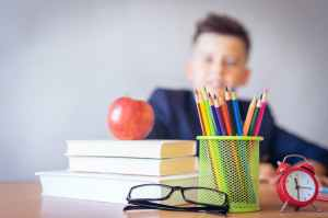 A child sitting at a desk. Books, pencils, glasses, a clock, and an apple are on the desk.