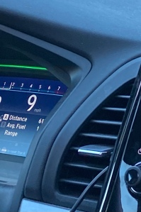 A car dashboard with the speedometer reading 9 mph.
