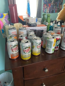 Open seltzer cans on a dresser in a bedroom.