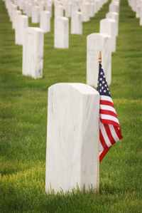 A grave with an American flag in a cemetery.
